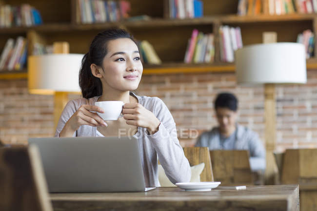 Chinese woman drinking coffee in cafe — Stock Photo
