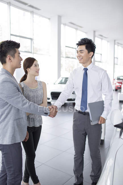 Chinese couple shaking hands with car dealer in showroom — Stock Photo