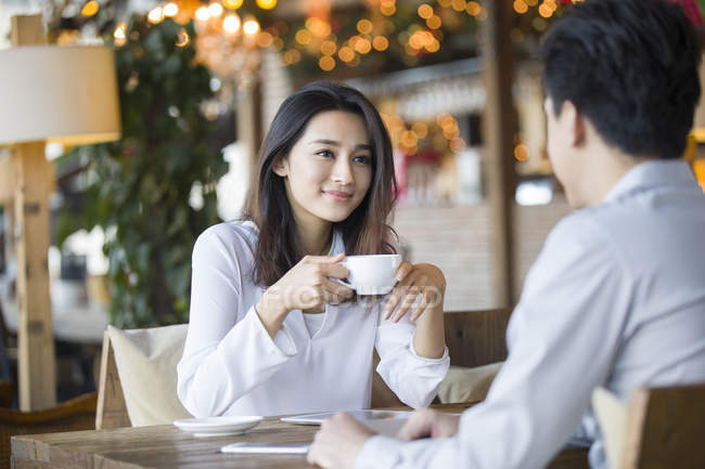 Chinese woman and man talking with coffee in cafe — Stock Photo