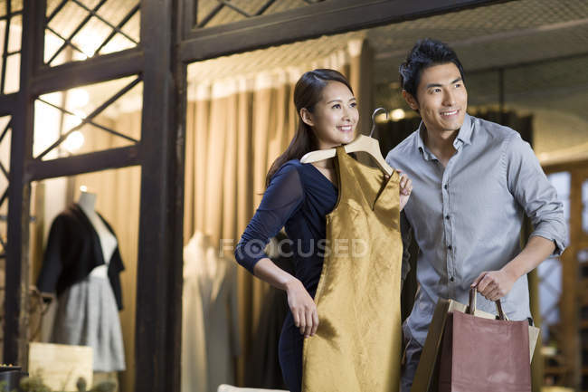 Cinese coppia scegliendo abito in negozio di abbigliamento — Foto stock