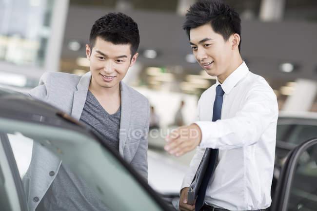Concessionario auto cinese aiutare il cliente a scegliere auto in showroom — Foto stock