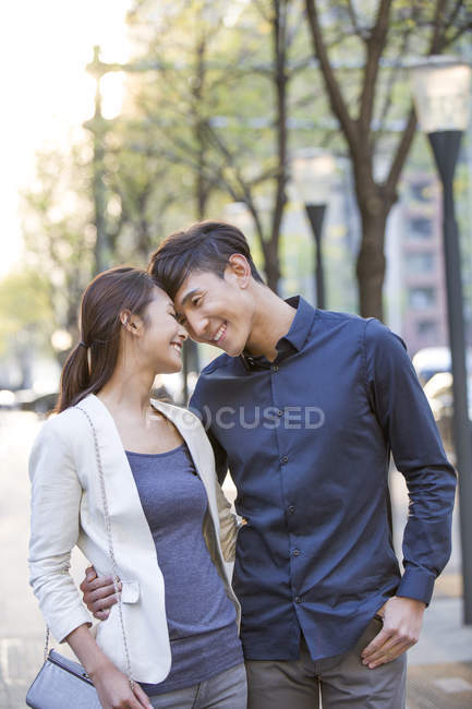 Chinese couple standing face to face on street — Stock Photo