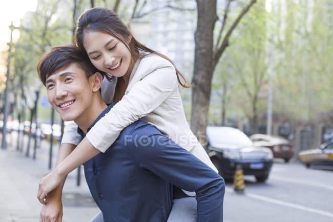 Cinese uomo holding piggy indietro fidanzata su strada — Foto stock