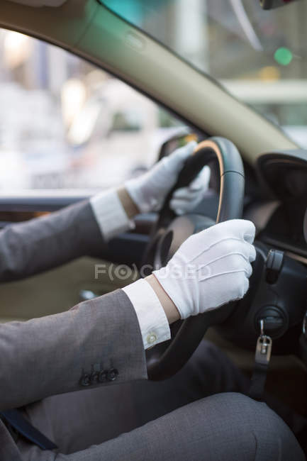 Close-up view of chauffeur hands driving car — Stock Photo
