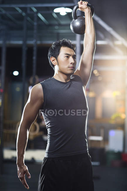 Chinese man training with kettlebell in crossfit gym — Stock Photo