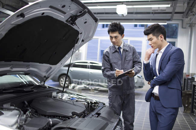 Chinese auto mechanic and car owner looking at engine — Stock Photo