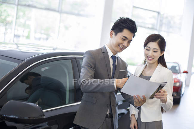 Chinese businesswoman making deal with car seller in showroom — Stock Photo