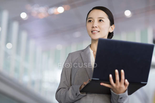 Chinese businesswoman standing with laptop indoors — Stock Photo