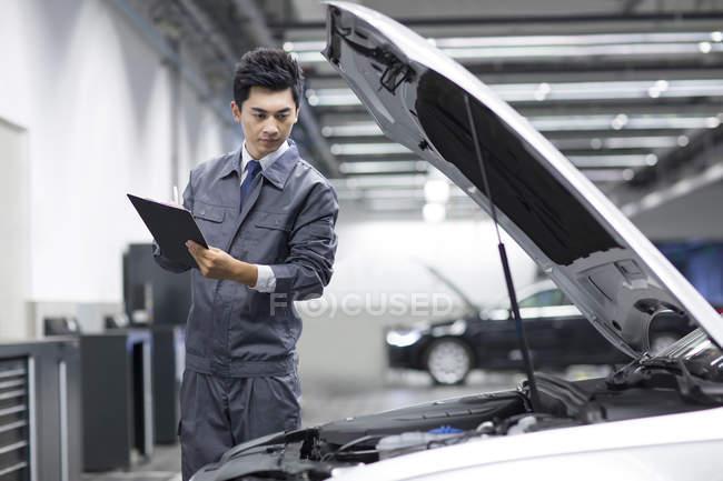 Chinese auto mechanic taking notes while examining car — Stock Photo