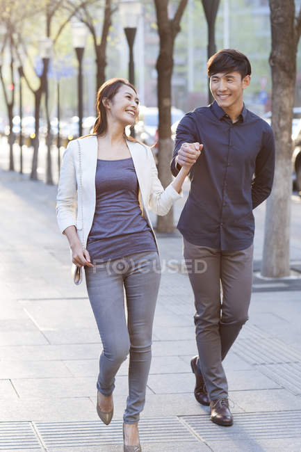 Chinese couple holding hands while walking on sidewalk — Stock Photo