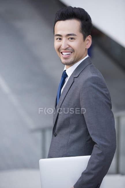 Homme d'affaires chinois tenant un ordinateur portable et souriant — Photo de stock