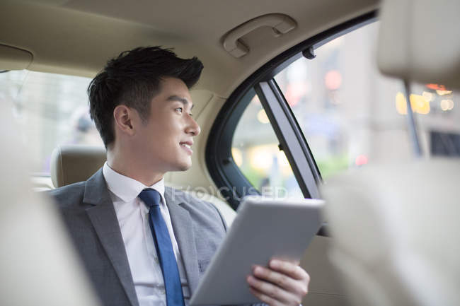 Chinese businessman using digital tablet in car — Stock Photo
