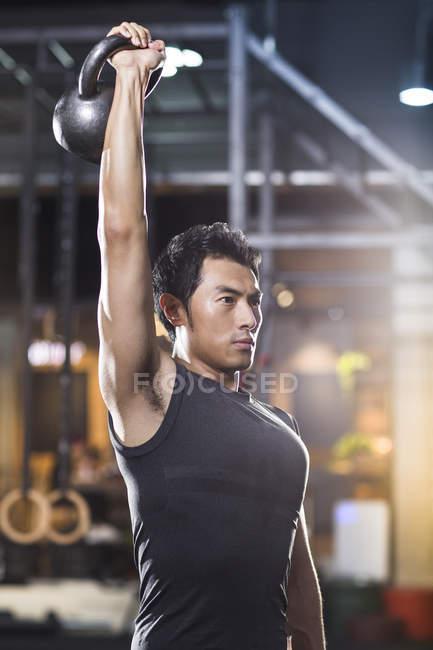 Chinesischer Mann heben Kettlebell in Crossfit gym — Stockfoto