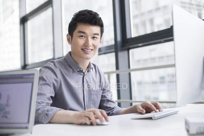 Homme d'affaires chinois à l'aide d'ordinateur de bureau — Photo de stock