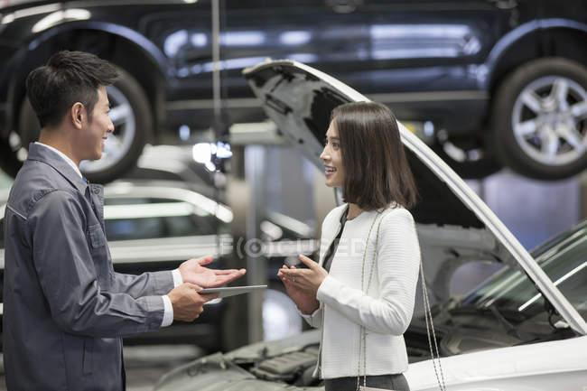 Meccanico auto cinese parlando con il proprietario dell'auto — Foto stock