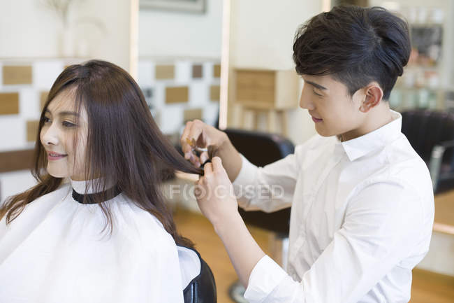 Chinese barber cutting female customer hair, side view — Stock Photo
