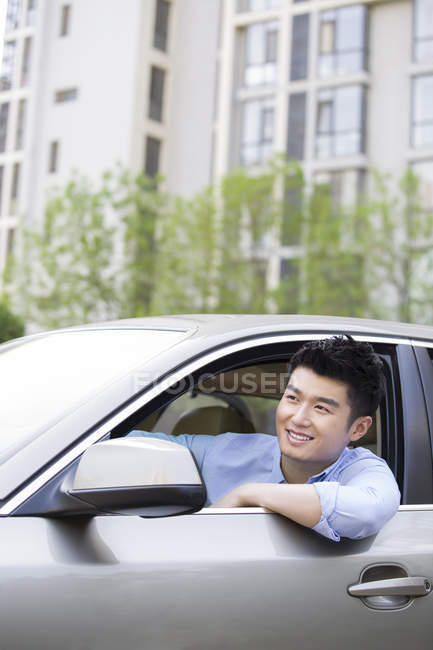 Chinese man driving and leaning out of car — Stock Photo