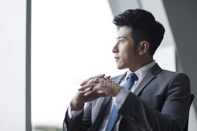 Китайський бізнесмен, дивлячись через вікно в офісі — стокове фото