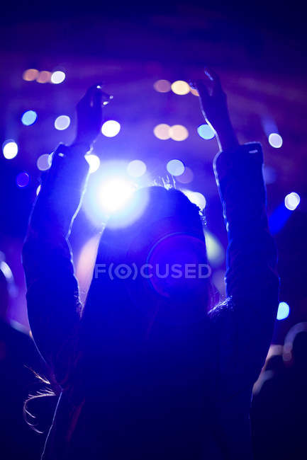 Woman with arms raised at music festival — Stock Photo