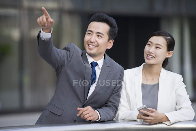 Chinese businessman pointing and looking at view with woman — Stock Photo