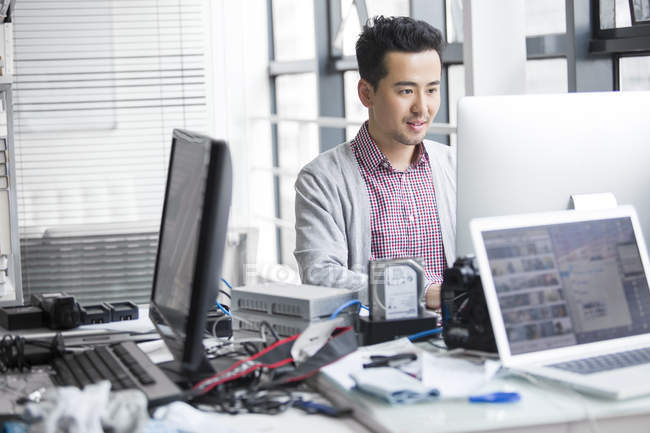 Chinese man working in office with computer — Stock Photo