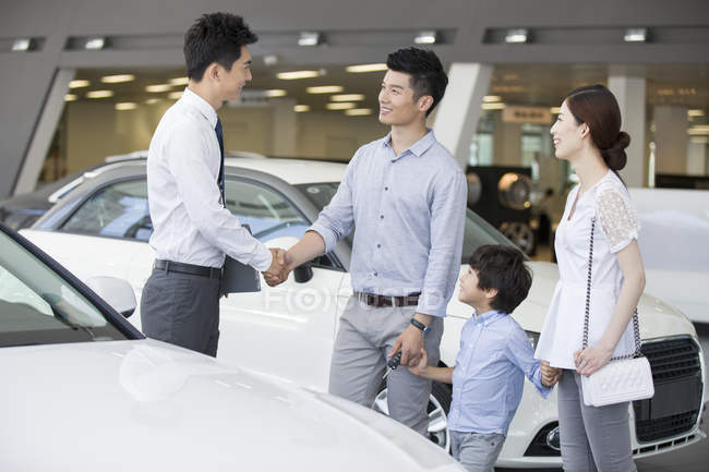 Chinese family shaking hands with car seller in showroom — Stock Photo