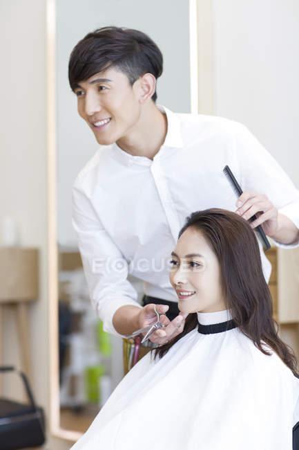 Barbiere cinese con cliente femminile che guarda nello specchio — Foto stock