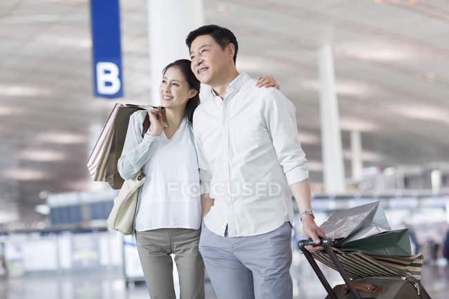 Пожилая пара китайских, стоя в аэропорту с сумки — стоковое фото