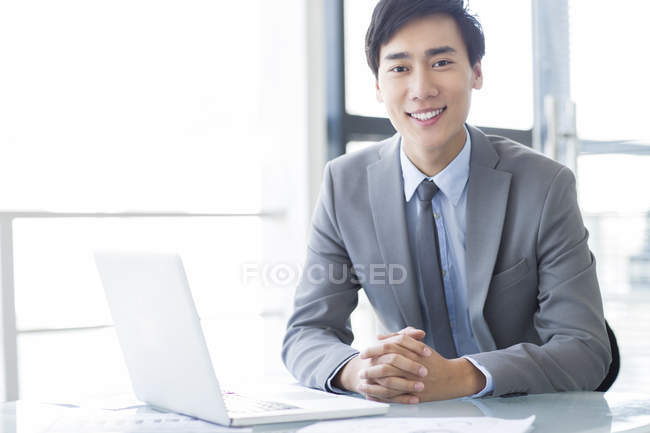 Chinese businessman sitting with laptop in office — Stock Photo