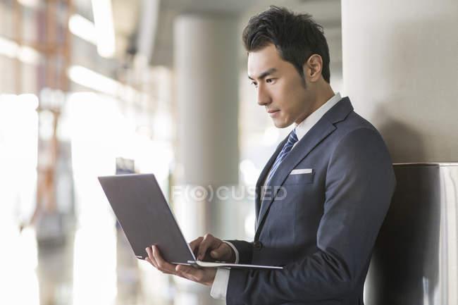 Homme d'affaires chinois utilisant un ordinateur portable à l'intérieur — Photo de stock