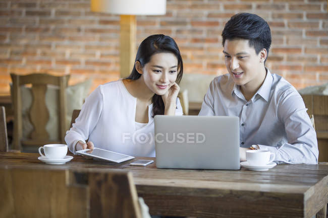 Chinese man and woman using laptop in cafe — Stock Photo