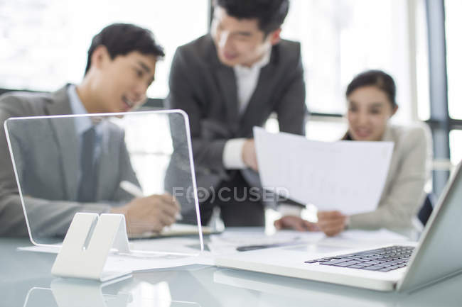 Unfocused business people at meeting with laptop on table — Stock Photo
