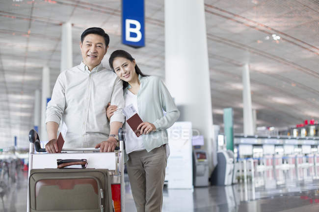 Mature chinese couple standing at airport with tickets — Stock Photo