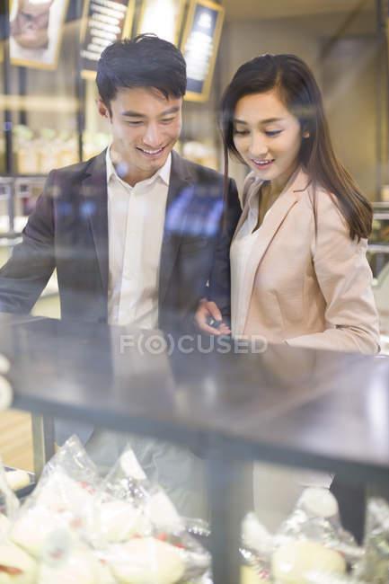 Casal chinês escolher bolos na padaria — Fotografia de Stock