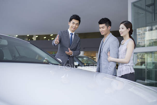 Chinese couple choosing car with dealer in showroom — Stock Photo