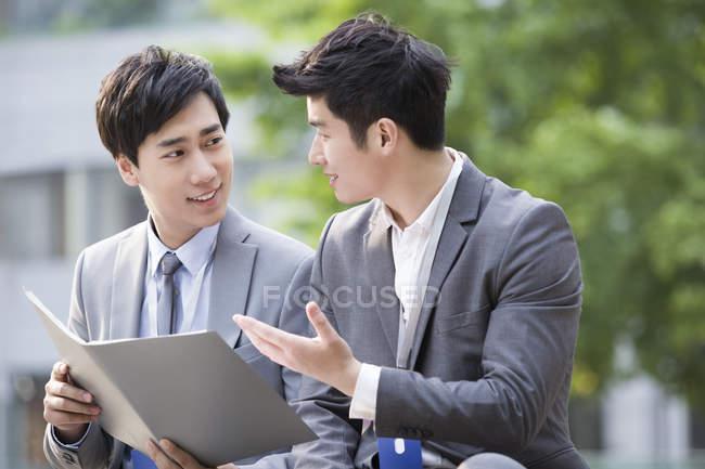 Uomini d'affari cinesi discutono lavoro su banco — Foto stock