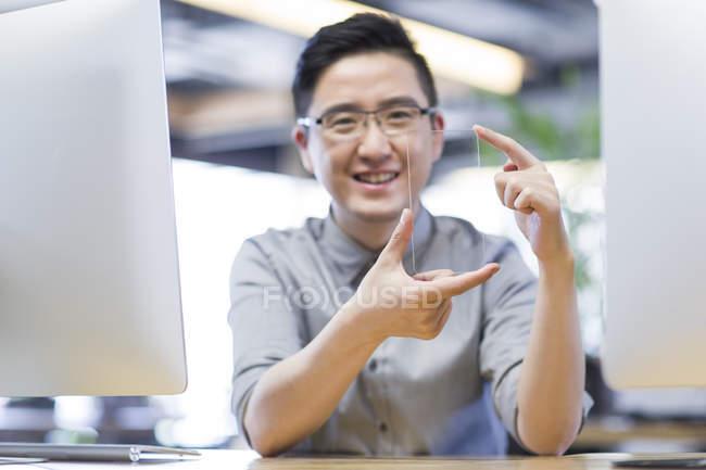 Trabajador de TI chino desarrollando smartphone en la oficina - foto de stock