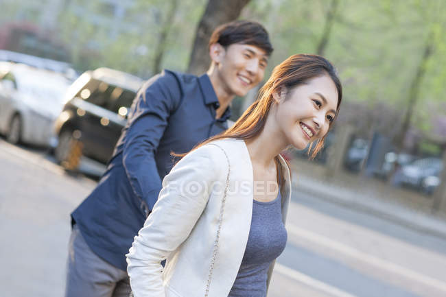 Chinese couple standing on street and holding hands — Stock Photo