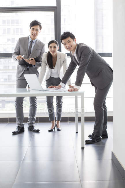 Chinese business people with laptop in board room — Stock Photo