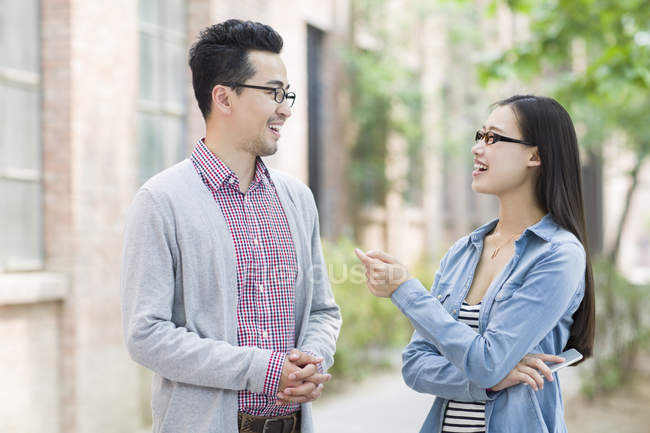 Chinese colleagues talking and laughing on street — Stock Photo