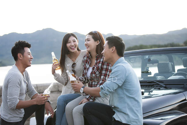 Chinese friends sitting on car with beer — Stock Photo