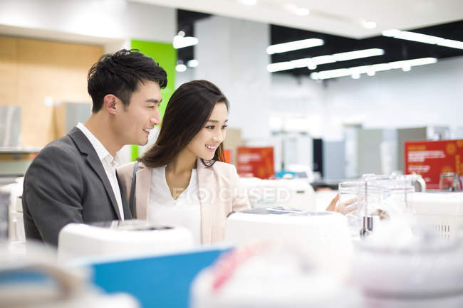 Chinese couple shopping in electronics store — Stock Photo