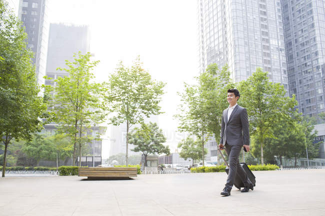 Chinese businessman walking and pulling suitcase on street — Stock Photo