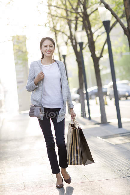 Mature chinese woman walking on street after shopping — Stock Photo