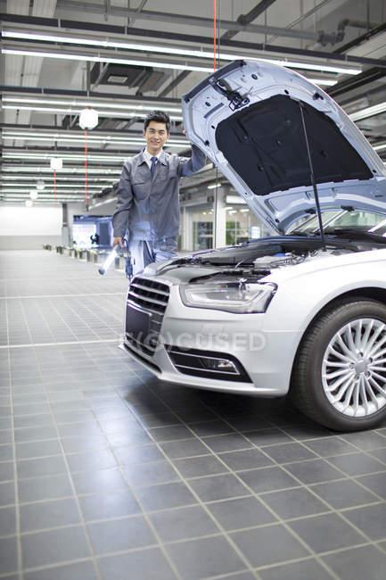 Китайський авто механік стоячи з ліхтариком в майстерні — стокове фото