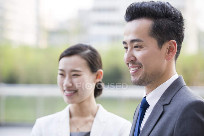 Chinese business people looking at view and smiling — Stock Photo