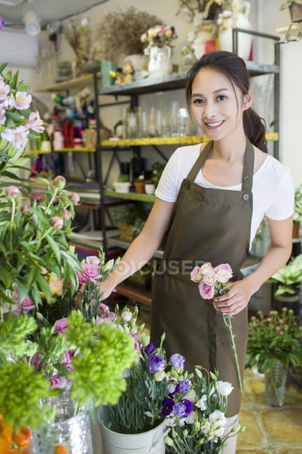 Владелец китайского магазина держит цветы в цветочном магазине — стоковое фото