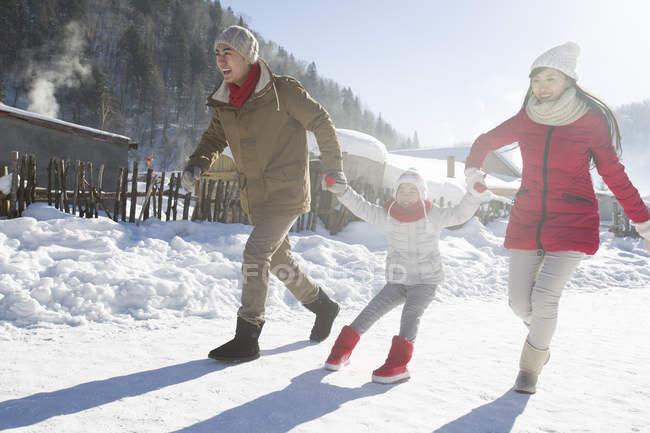 Pais chineses puxando a filha na neve — Fotografia de Stock