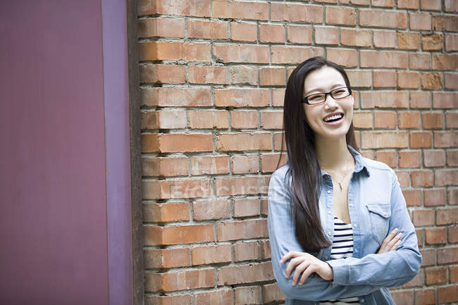 Chinese woman standing with arms folded and laughing — Stock Photo