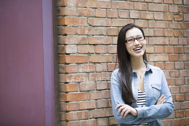 Donna cinese in piedi con le braccia incrociate e ridendo — Foto stock